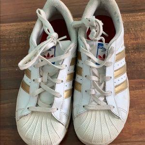 Gold adidas superstars worn
